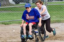 "Mathieu Auclair hustles to first with the help of his ""buddy"" each player has a buddy to help in the enjoyment of playing in the Challenger Baseball program. The 17-year-old Auclais is a two sport athlete as he participates in sledge hockey in the winter."