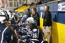 Michel Dubé (centre) est entraineur pour des équipes de hockey féminine depuis sept ans.