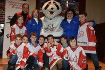 La mascotte officielle du tournoi atome, TOMI, entouré des responsables et des jeunes hockeyeurs des Lions de Saint-Jérôme