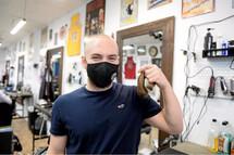 Tomy Néron a été l'un des premiers à embarquer dans le Défi têtes rasées. Il était de ceux qui avaient la plus longue chevelure. Il a d'ailleurs conservé sa couette pour se remémorer ce moment avec ses coéquipiers. Crédit photo : Le Quotidien, JEANNOT LÉVESQUE