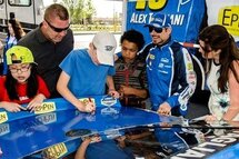 NASCAR driver Alex Tagliani watches on as students from Woodland Heights Public School sign the back of his #18 Lowe's EpiPen St-Hubert Dodge out front of the Lowes London South store on June 2. - Mike Maloney